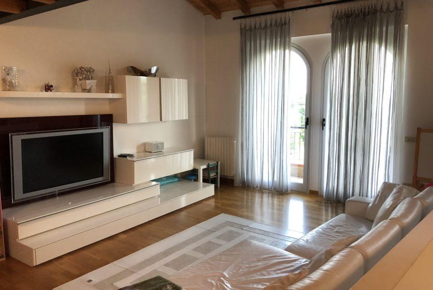 soggiorno con grande parete tv, vetrate e comoda zona divano villetta a schiera Palazzago